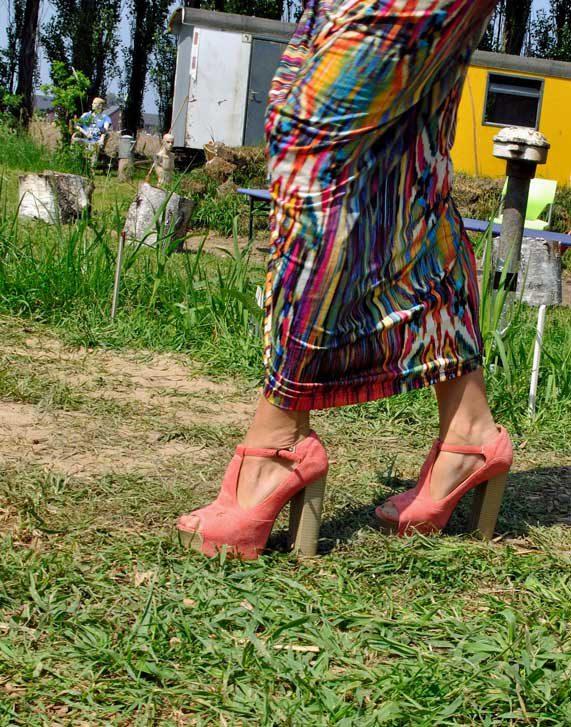 Dame in kleurrijke lange rok en schoenen met hoge hakken op wild grasveld met etalagepop tijdens rondje noord 2018 bij Nijmeegse StadsNomaden