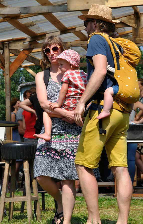 Hip stel met kleuter en baby in draagzak op de rug bij barkruk in kantine tijdens rondje noord 2018 bij Nijmeegse StadsNomaden