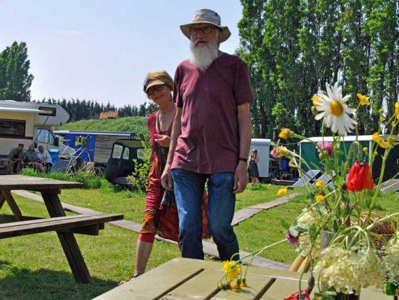 Twee jonge ouderen met pet en hoed bij picknicktafels met veldboeket en woonwagens tijdens rondje noord 2018 bij Nijmeegse StadsNomaden
