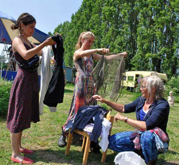 Vrouwen in zomerjurken bekijken en keuren kleding van kledingruilrek met woonwagen en circustent op de achtergrond tijdens rondje noord 2018 bij de Nijmeegse StadsNomaden