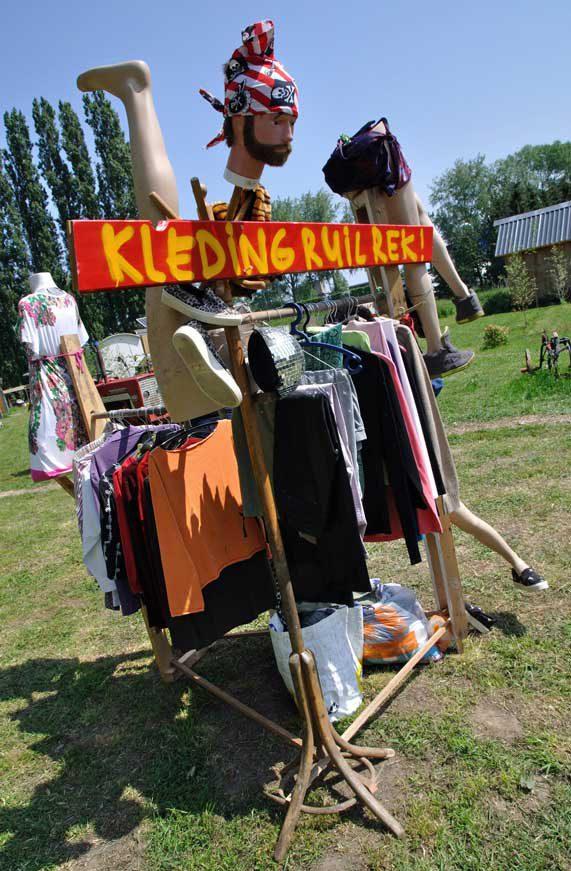 Bord met tekst kledingruilrek op rek vol kleerhangers met kleren en etalagepoppen tijdens rondje noord 2018 bij Nijmeegse StadsNomaden