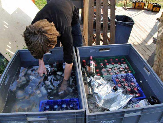 Kratten bier met bierflesjes ondergedompeld in koud water met kratten Hertog Jan tijdens rondje noord 2018 bij Nijmeegse StadsNomaden
