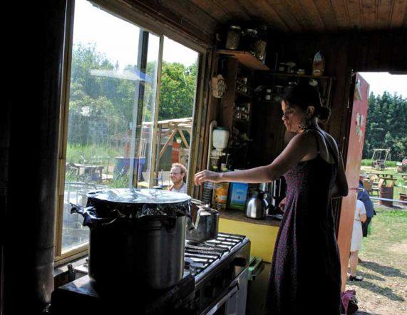 latin beauty meisje in woonwagen achter fornuis met grote pan in fraai tegenlicht en jongen met rastakapsel tijdens rondje noord 2018 bij Nijmeegse StadsNomaden