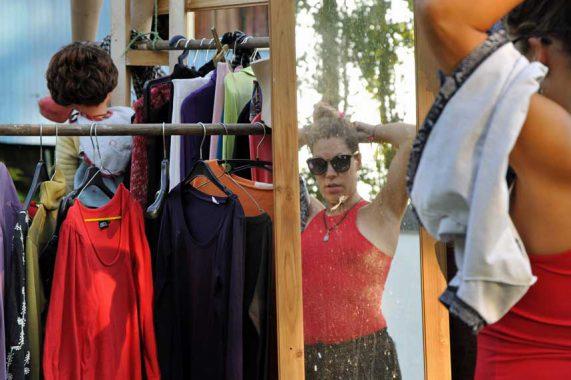 Spiegelbeeld van vrouw voor spiegel van kledingruilrek met veel kleerhangers tijdens rondje noord 2018 bij Nijmeegse StadsNomaden