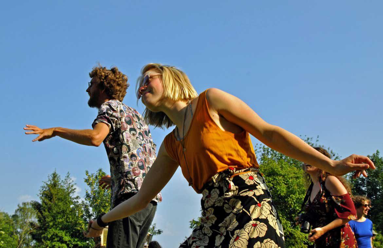 twee dansers met bloerijke kleding voor blauwe lucht genieten van optreden George Kush Trio in circustent tijdens rondje noord 2018 bij Nijmeegse StadsNomaden