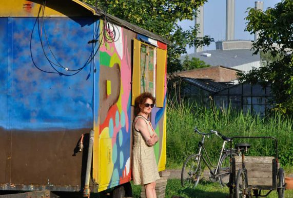 Vrouw met zonnebril voor kleurrijke woonwagen geniet van de zon tijdens rondje noord 2018 bij Nijmeegse Stadsnomaden