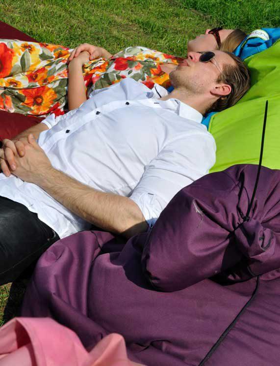Zitzak waar mensen op liggen man in wit overhemd en vrouw in bloemetjesjurk tijdens rondje noord 2018 bij Nijmeegse StadsNomaden
