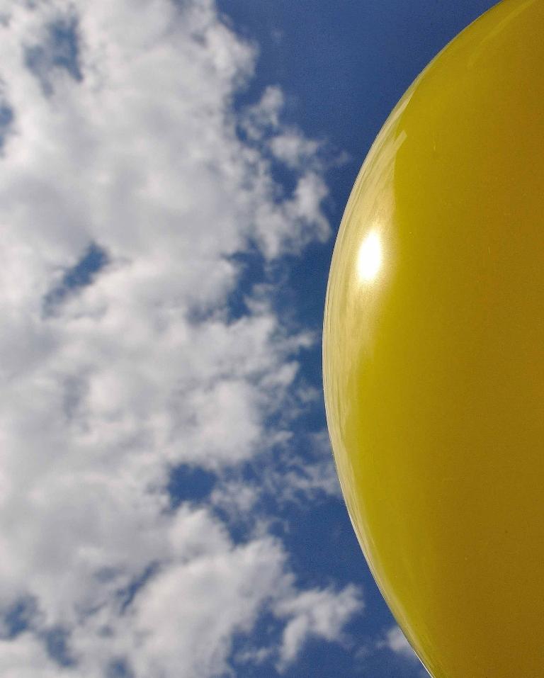 Ballon als zon in blauwe wolkenlucht in de zomer met licht weerspiegeld op het oppervlak