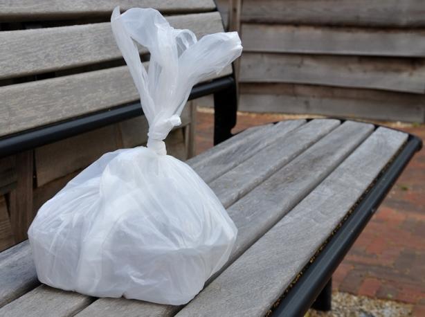 Wit plastic zakje met lekkers op bank in betegelde tuin van zorginstelling